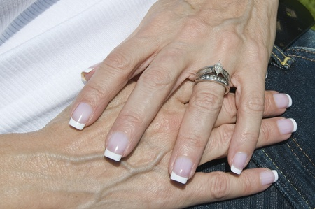 French manicured female hands with wedding band and engagement ring photo