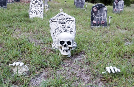 Spooky cemetery with skull and hands poking through the ground with tombstones in the background photo