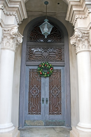 Ornate Iron work covering double door entrance with Christmas wreath and gothic columns