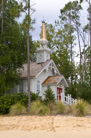 Small church hidden among pine trees on a sandy beach with red entry doors photo