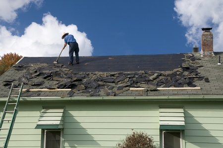 RENOVATE: Removing old shingles to prepare a roof for a new installation with blue sky