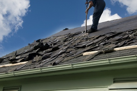 Extracción de tejas viejas para preparar un techo para una nueva instalación con el cielo azul