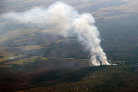 Forest fire viewed from an airplane showing smoke drifting away Stock Photo