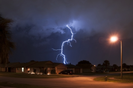 Massive lightning strike very close to homes in a neighborhood Stock Photo