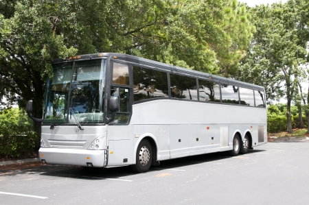 A gray tour bus or camper parked in an empty parking lot