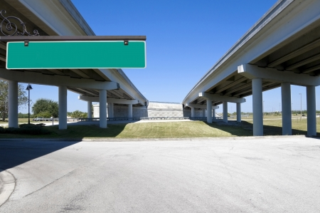 Multi-lane expressway overpass showing structural columns with blue sky with green street sign for text photo