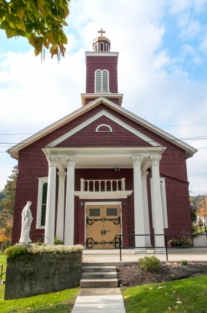 A small Christian country church on a hillside during the fall season photo