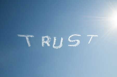 Skywriting the word Trust on a blue sky with a sun burst