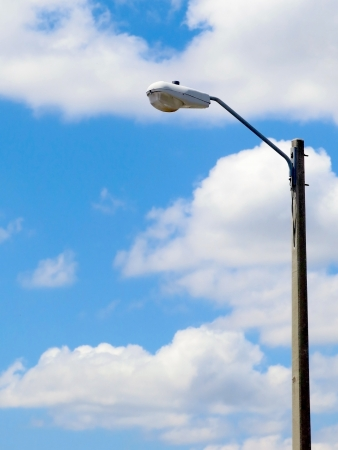 halogen lighting: Street light mounted on a concrete pole with partly cloudy blue sky                       Stock Photo