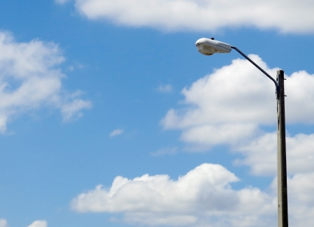 streetlight: Street light mounted on a concrete pole with partly cloudy blue sky          Stock Photo