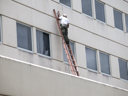 Men repairing the side of a commercial building from a ladder
