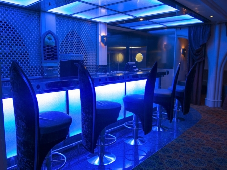 Nightclub Bar Lighted With Blue Lighting and Highback Stools