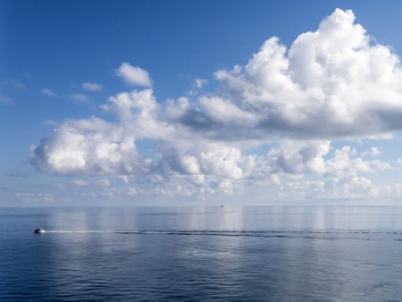 partially: Extremely Calm Ocean Showing Partially Cloudy Blue Sky and Paragliding Speed Boat on Water