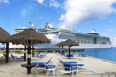caribbean cruise: Two Cruise Ships docked next to a sandy beach with blue water and sky