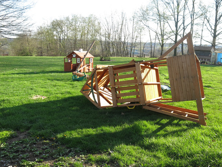Wind damaged childrens playhouse and swingset after a spring storm Stock Photo