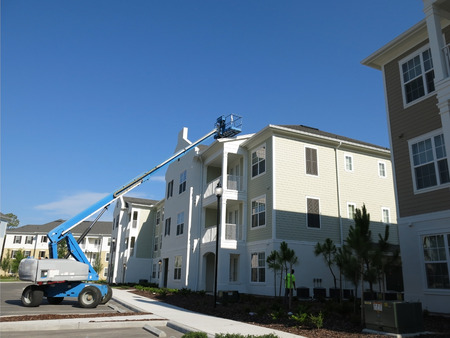Blue bucket lift extended to a roof to make repairs on a clear day photo