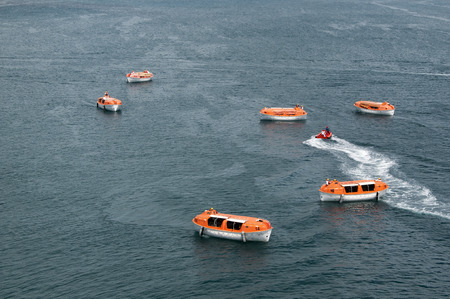 Orange and white lifeboats training and testing for safety requirements