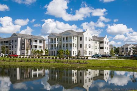 Appartementen en flats met reflectie in een nabijgelegen meer en deels bewolkte blauwe hemel