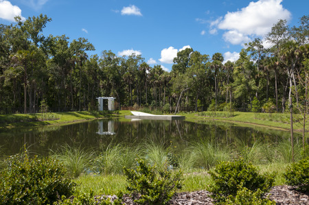 Water retention pond near woods and bridge with partly cloudy sky Stock Photo