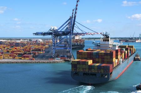 무거운 크레인 및 들어오는 배와 프리 포트 바하마 컨테이너 조선소의 포트 예인선 보트의 도움을 독