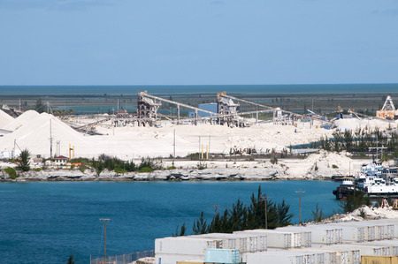 mining ship: Limestone Mining on an Island with storage silos and ship waiting to be loaded and deep blue Ocean Water