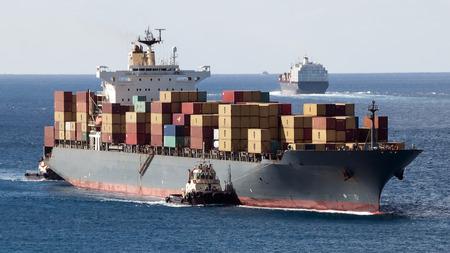 Port de Freeport Grand Bahama Island avec de nombreux contenants de navires qui entrent et sortent du port de rempli de marchandises et un remorqueur d'assistance Banque d'images
