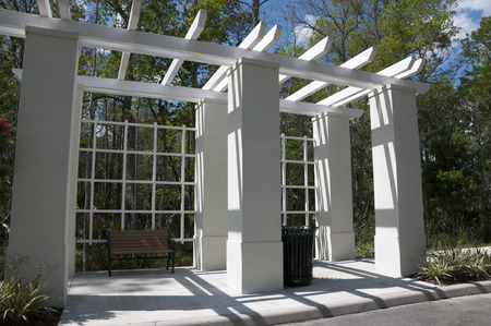 receptacle: Elegant lattace frame bus stop with a wood bench and green trash receptacle