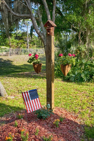two story: Two story bird house mounted on top of a post with two vegetation planters hanging on wire brackets and the american flag