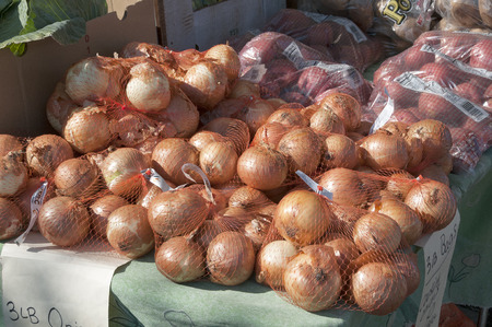 bagged: Farmers market display of three pound bagged onions and apples Stock Photo