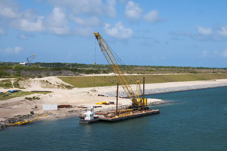 Dredging shore line and adding stone barrier wall using a barge to transport excavator photo