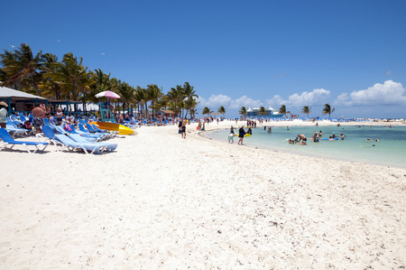 caribbean cruise: COCO CAY BAHAMAS  MAY 26 2015: Sandy beach with people enjoying sun and fun with their Royal Caribbean cruise ship anchored in the background