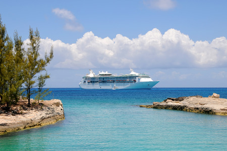 Cruise Ship anchored off shore at a lagoon entrance with blue water and sky