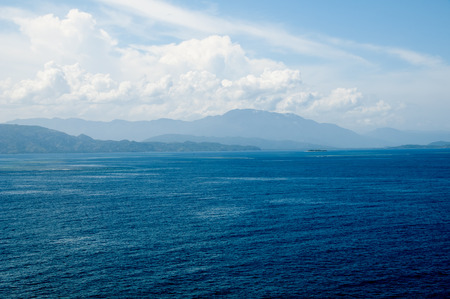 North coast of the island of Haiti with blue haze covering the mountains and deep blue ocean water Stock Photo