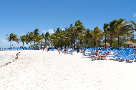caribbean cruise: COCO CAY, BAHAMAS - MAY 26, 2015: Sandy beach with people enjoying sun and fun with their Royal Caribbean cruise ship anchored in the background