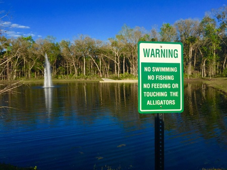 Warning sign of alligators present in lake Stock Photo
