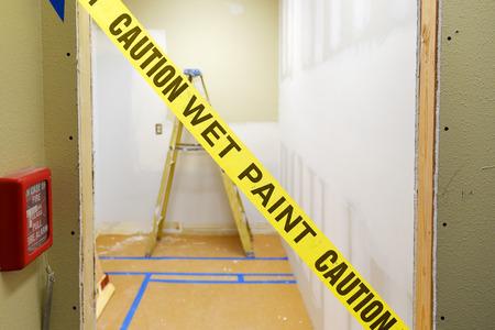 portone: Giallo nastro della vernice cautela umido attraverso una porta con scaletta di costruzione in background Archivio Fotografico