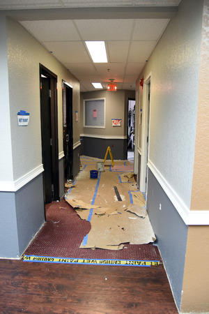 paintbrush spray: Renovating and repainting office building hallway walls using spray method and taping to provide protection of carpet