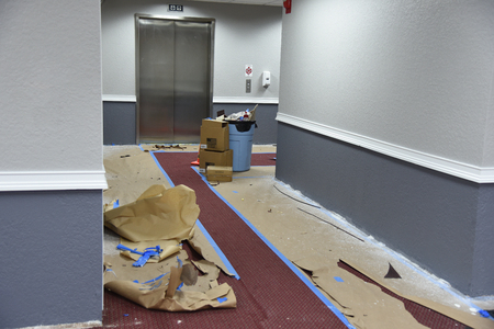 Renovating and repainting office building hallway walls using spray method and taping to provide protection of carpet