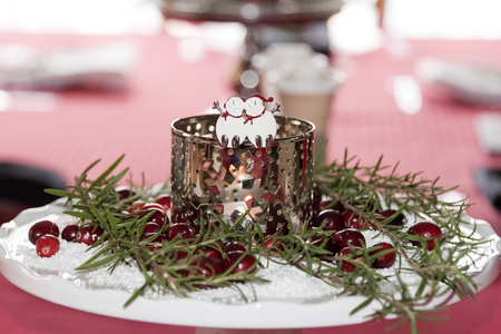 Table center piece of a candle surrounded by cranberries and green branches on a white pedestal for the holidays Stock Photo