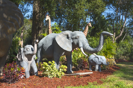 Garden statues of an Adult elephant and two baby elephants with Giraffes in the background Stock Photo