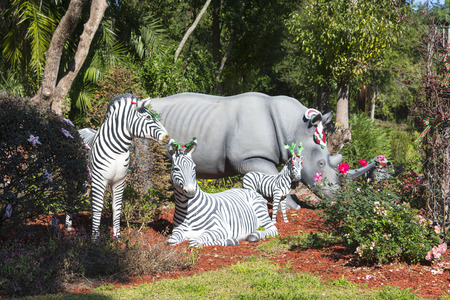Zebras and a rhinoceros grazing in the garden decorated with Christmas Ornaments on their heads