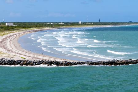 Multiple ocean waves crashing in to a shore near a stone breakwall