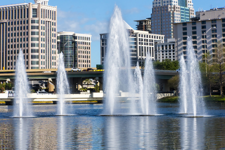 Multiple water fountains in from of towering building highrises