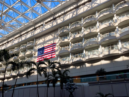 United States Flag displayed in an airport between balconies and steel frame work