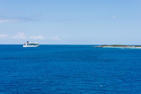 Cruise ship sailing the blue ocean near an island