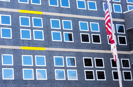 Flag and Windows at Healthcare hospital showing blue sky reflection