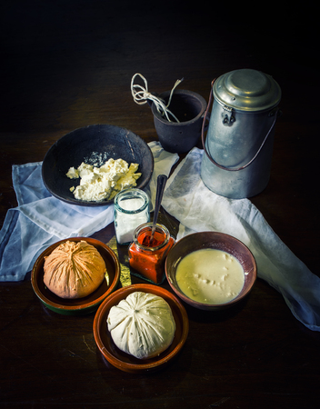home made cheese over a rustic wooden table with its ingredients, milk, salt, paprika, curd and an old milk churn