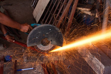 hand catching small grinder to cutting steel photo