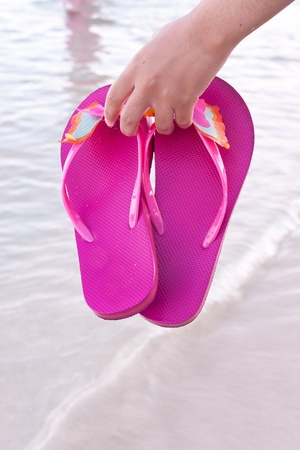 Young woman on the beach with colorful flip flop photo