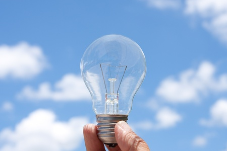 Hand holding light bulb in blue sky and cloud  Stock Photo - 10472846